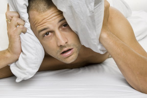 Man trying to sleep with a pillow over his head