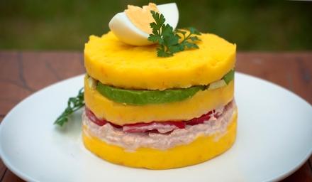 圖 1:Causa limeña:金黃色馬鈴薯泥夾著各式蔬菜、海鮮或雞肉,層層堆疊如華麗的千層蛋糕。圖片來源:http://limaperutours.com/en/tours-en-peru/tour-gastronomico-clase-de-cocina/