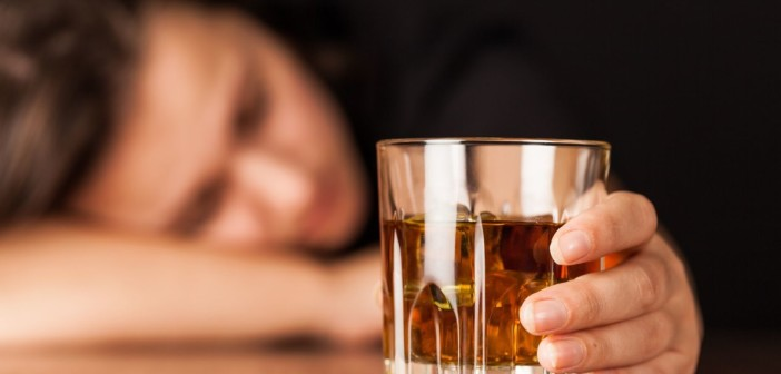 93376283 - drunk woman sleeping at bar counter holding a glass of whisky