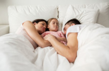 69815681 - happy family sleeping in bed at home