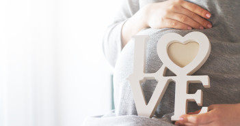 Young pregnant woman holds wooden letters LOVE. Love concept.