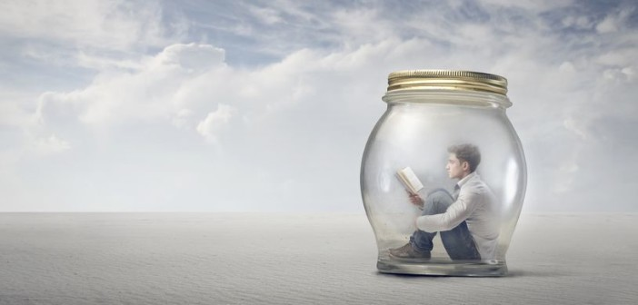 18539378 - young boy reads book sitting in a jar