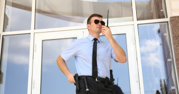 96312359 - male security guard with portable radio outdoors